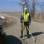 LE Land Surveying Services worker setting up an instrument